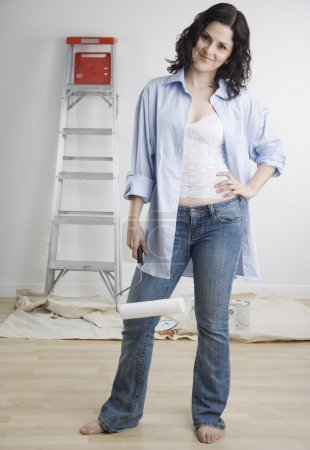 Portrait of woman with paint roller and ladder