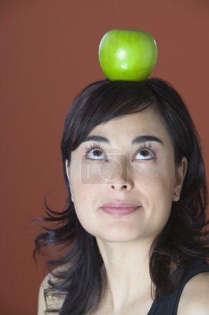 Woman posing with apple balanced on head