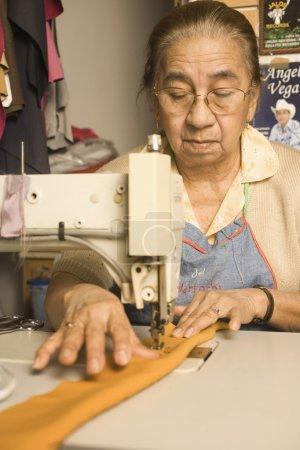 Senior woman using a sewing machine
