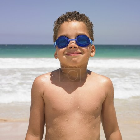 Smiling boy in goggles at beach