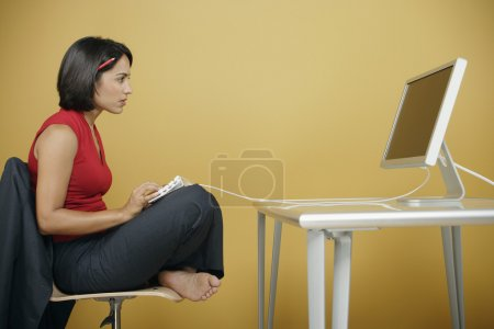 Businesswoman sitting crosslegged away from her computer