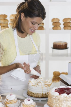 Woman decorating cake at bakery