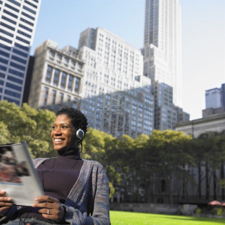 Woman listening to music in park while reading magazine
