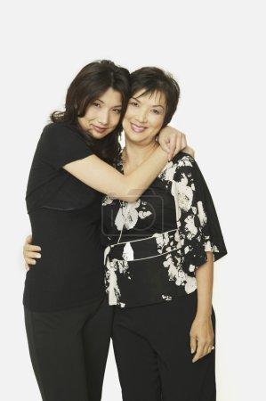Studio shot of Asian mother and adult daughter hugging