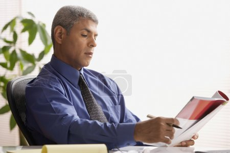 Mature businessman reading a magazine