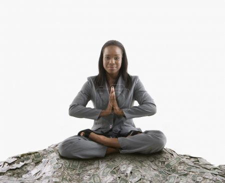 Businesswoman meditating on a mound of cash