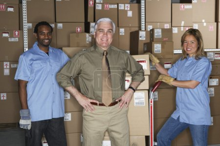 Businessman with warehouse workers in warehouse