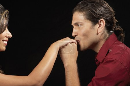 Young man kissing girlfriend's hand