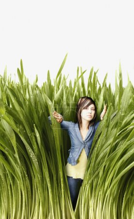 Young woman pushing back tall grass