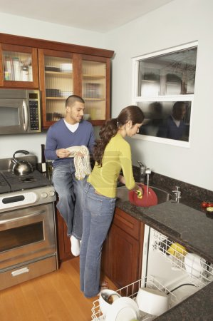 Young Hispanic couple washing dishes