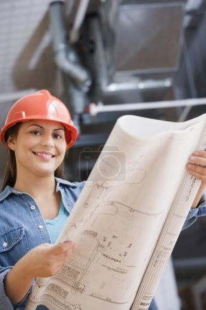 Hispanic female construction worker looking at blue prints