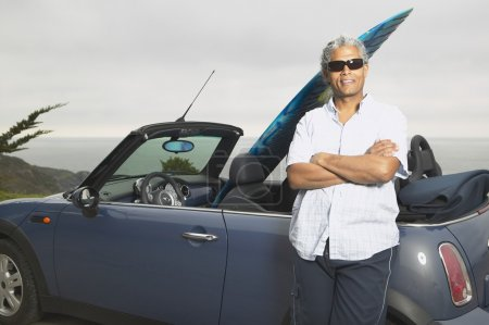 Senior man leaning on a convertible with a surfboard in it
