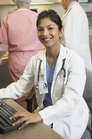 Young Indian female doctor at computer