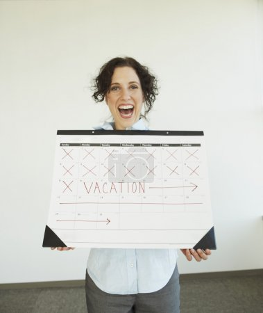 Businesswoman holding a calendar with her vacation marked on it