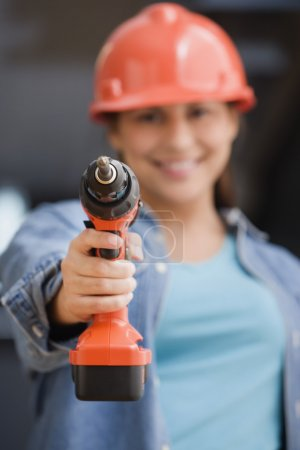 Hispanic female construction worker pointing a drill