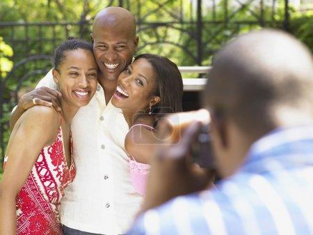 Family smiling as man take a photo