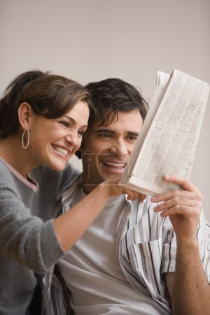 Young Hispanic couple looking at newspaper classified ads