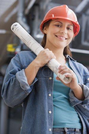 Hispanic female construction worker holding blueprints