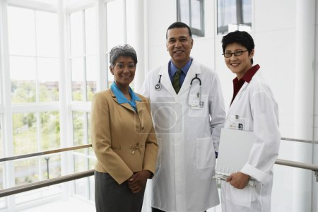 Businesswoman and doctors smiling for the camera