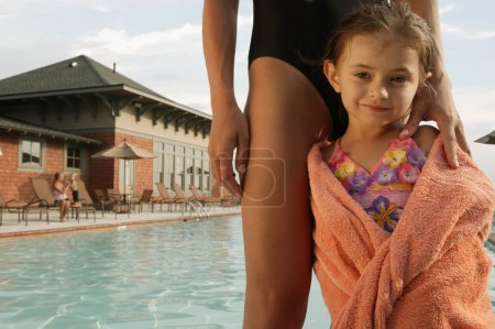 Young girl wrapped in a towel by swimming pool