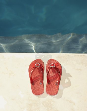 Flip-flops resting by a swimming pool