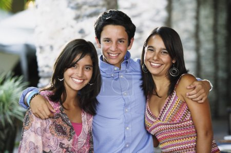 Teenage boy and his sisters smiling for the camera