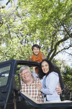 Hispanic grandparents with grandson in jeep