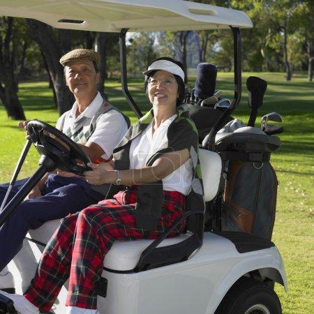 Senior Asian couple riding in golf cart