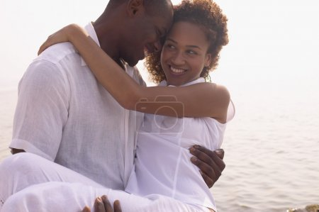 African couple hugging next to water