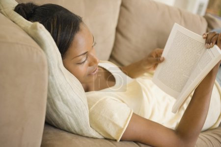 African woman laying on sofa reading