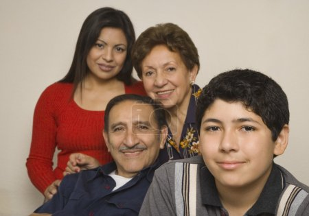 Hispanic grandparents with adult daughter and grandson smiling