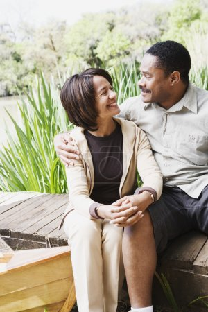 Middle-aged African couple smiling on dock