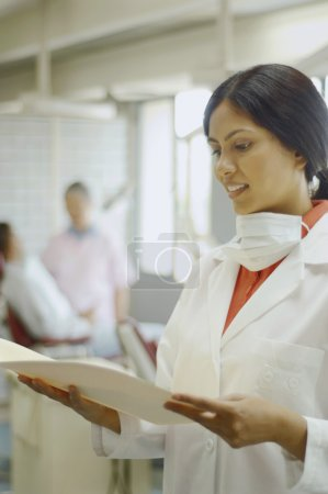 Indian female dentist looking at chart