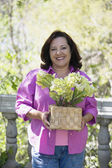 Middle-aged Hispanic woman holding potted plant outdoors