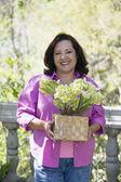 âge de la femme hispanique tenant la plante en pot à l'extérieur