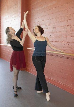 Mature female ballet teacher helping adult female student
