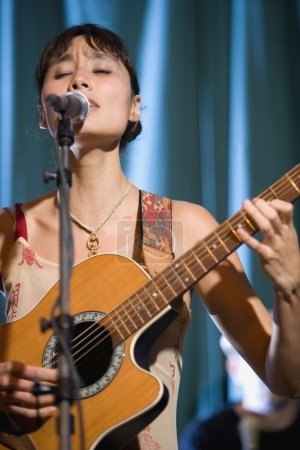 Asian woman playing guitar and singing