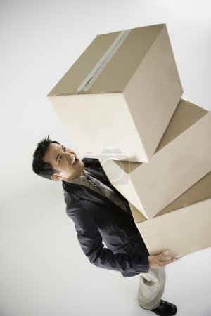 Asian businessman carrying stack of boxes