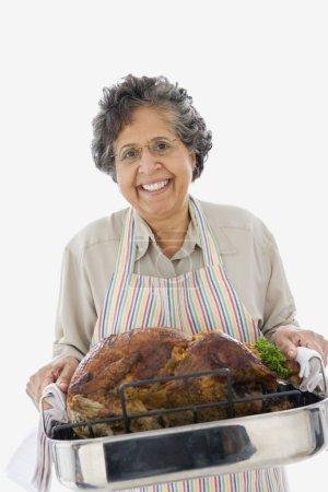 Senior Hispanic woman holding roasted turkey in pan