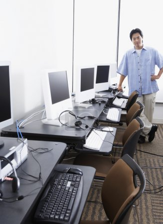 Young Asian man standing next to computer stations