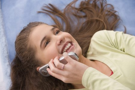 Hispanic girl laying down using cell phone