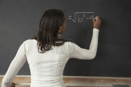 African female student writing on blackboard