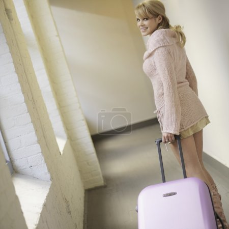 Woman pulling suitcase and smiling