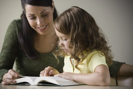 Hispanic mother reading with young daughter