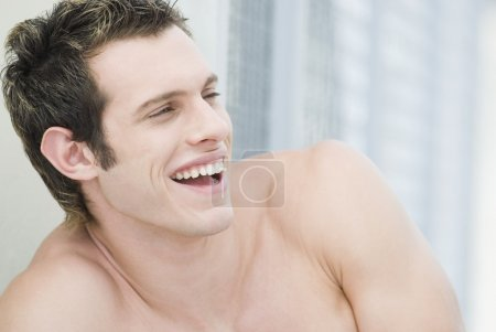 Bare-chested man laughing