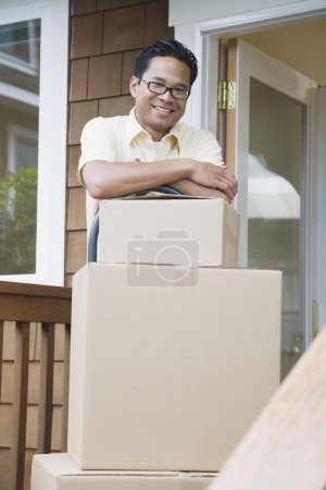 Asian man leaning on moving boxes on porch