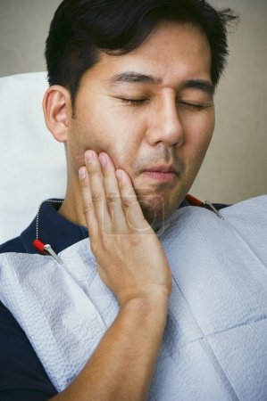Asian male dental patient holding jaw