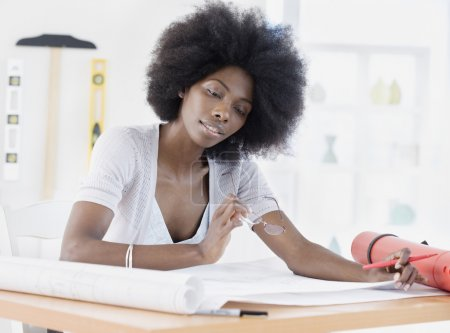 African female architect looking over blueprints