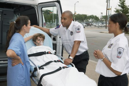 Female doctor talking to EMTs with boy on gurney