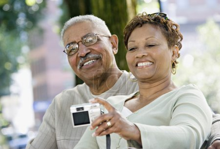 Senior African couple taking self-portrait in park